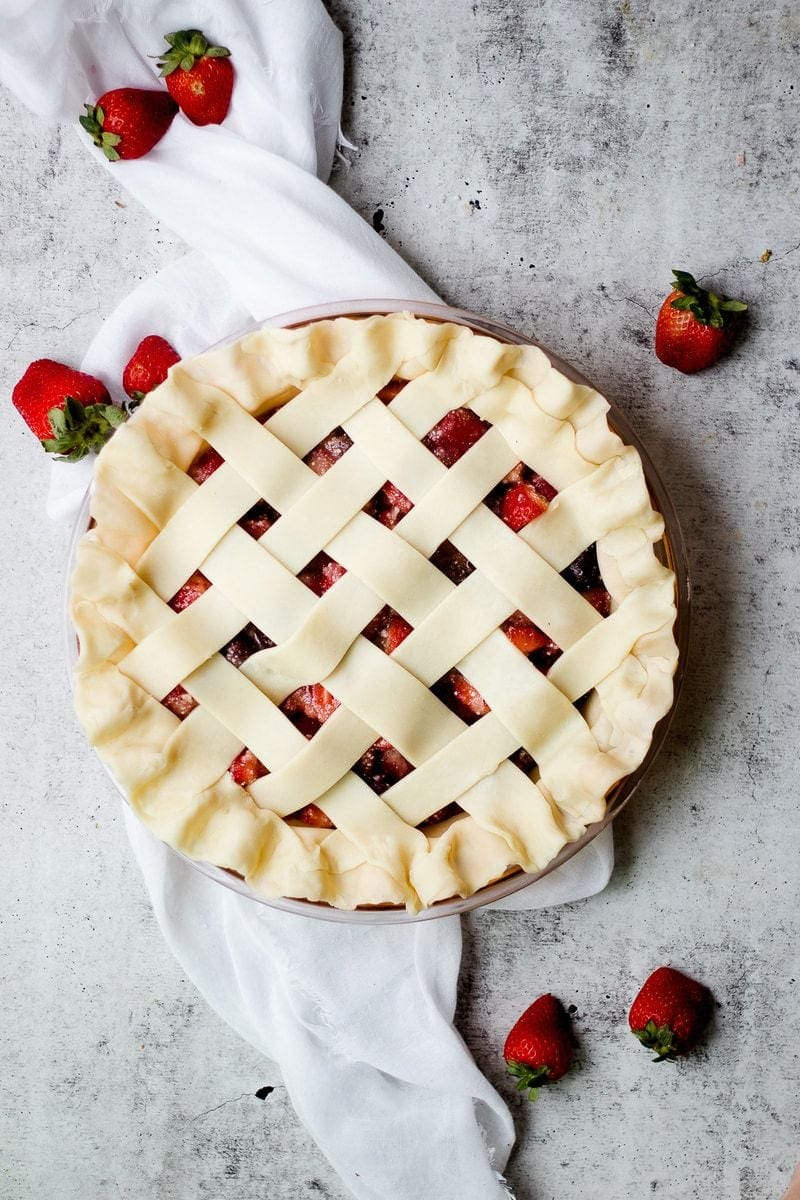 Tart Strawberry Rhubarb Pie with fresh strawberries scattered around