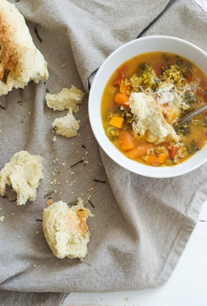 Quick Crusty Herb Bread torn into pieces with a bowl of soup at the side