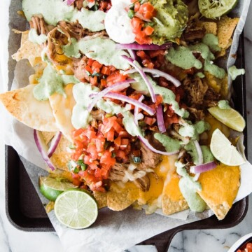 nachos on tray with toppings and creamy jalapeno sauce