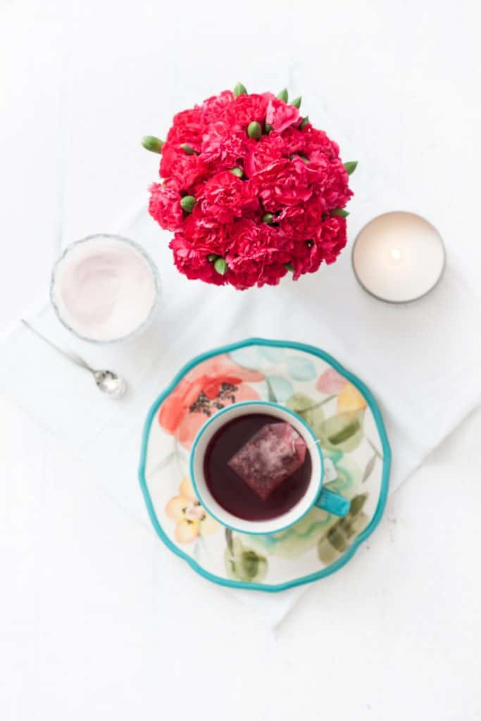 Tazo brand tea overhead shot in mug with flowers and candles