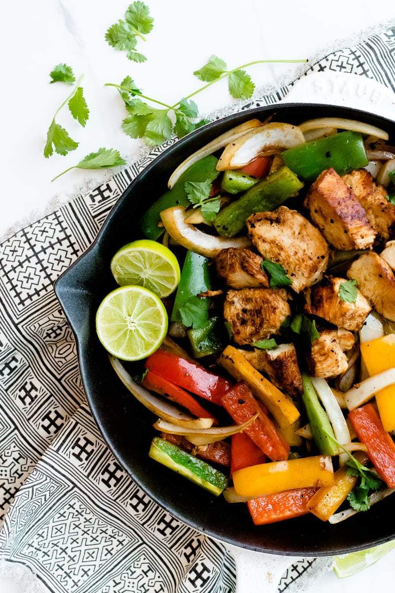 Skillet Chicken Fajitas on patterned cloth with cilantro and halved limes