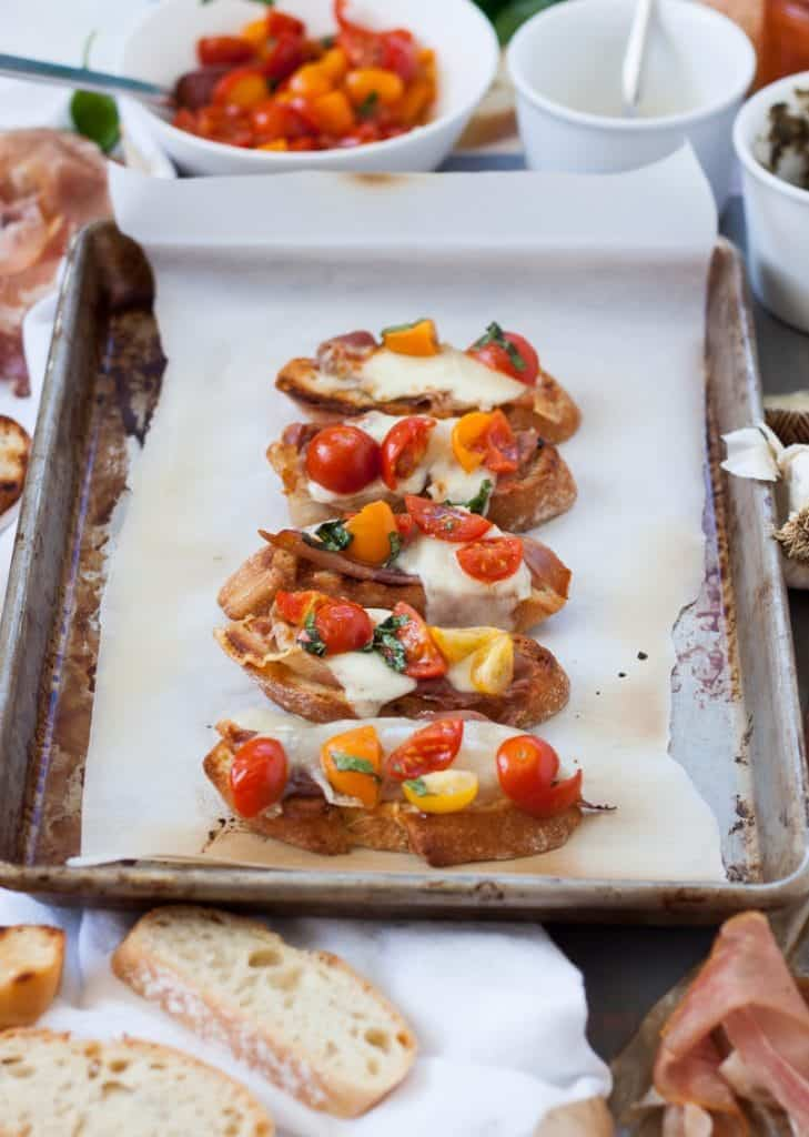 A tray of Spanish Tapas topped with cheese and tomatoes