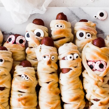 several mummy dogs (hot dogs wrapped in bread and have eyes) laying on a tray