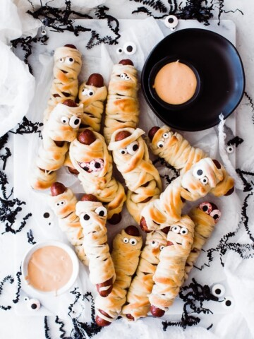 several mummy dogs (hot dogs wrapped in bread and have eyes) laying on a tray with two bowls of dipping sauce