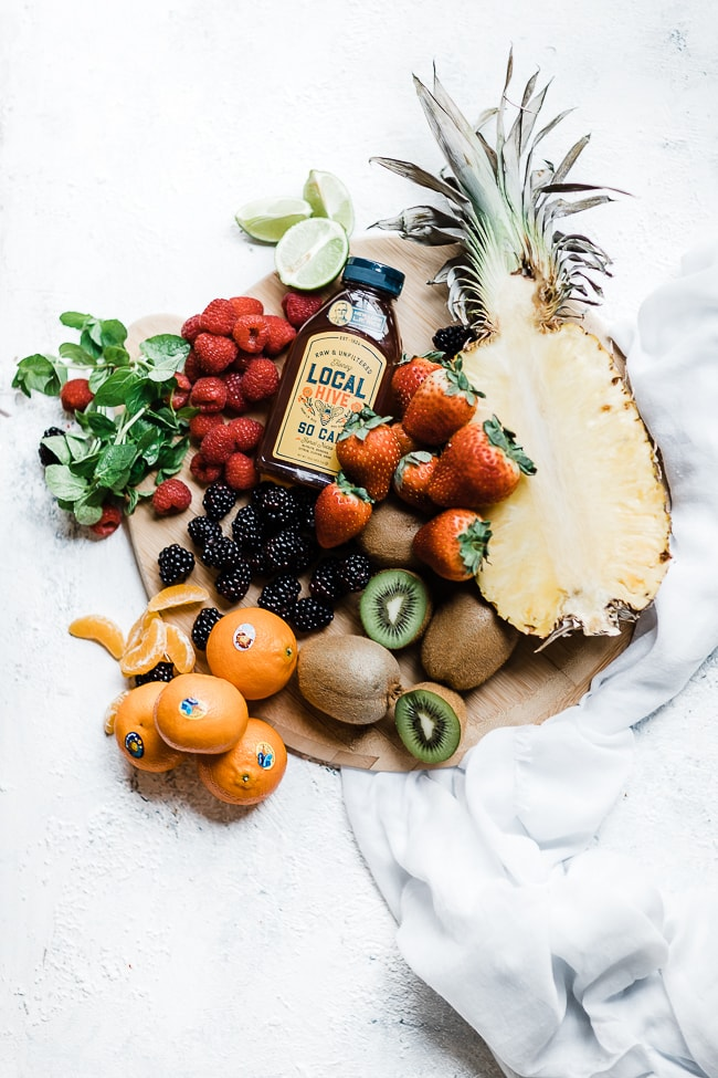 Mojito fruit salad ingredients on a round cutting board.