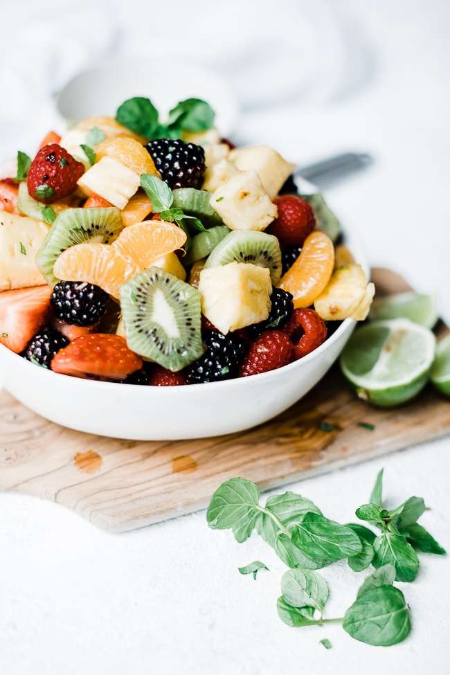 Mojito fruit salad in a white bowl on top of a wooden cutting board.