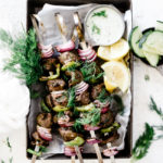 Lemon dill lamb kabobs in a baking tray, garnished with fresh dill and a side of tzatziki.