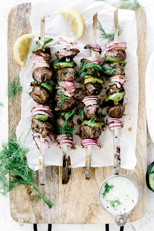 Lamb Kabobs on a wooden cutting board, garnished with dill and lemons.