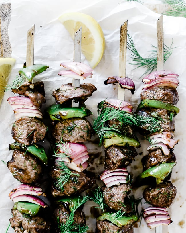 Close up of lamb kabobs on a cutting board.