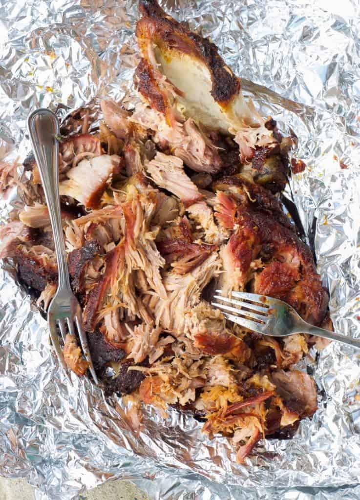 pulled pork in tinfoil, being shredded with forks