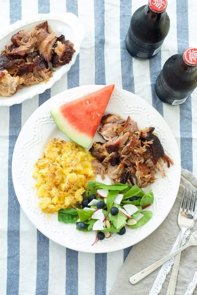 pulled pork on plate with salad, macaroni, and watermelon. soda in glass on the side
