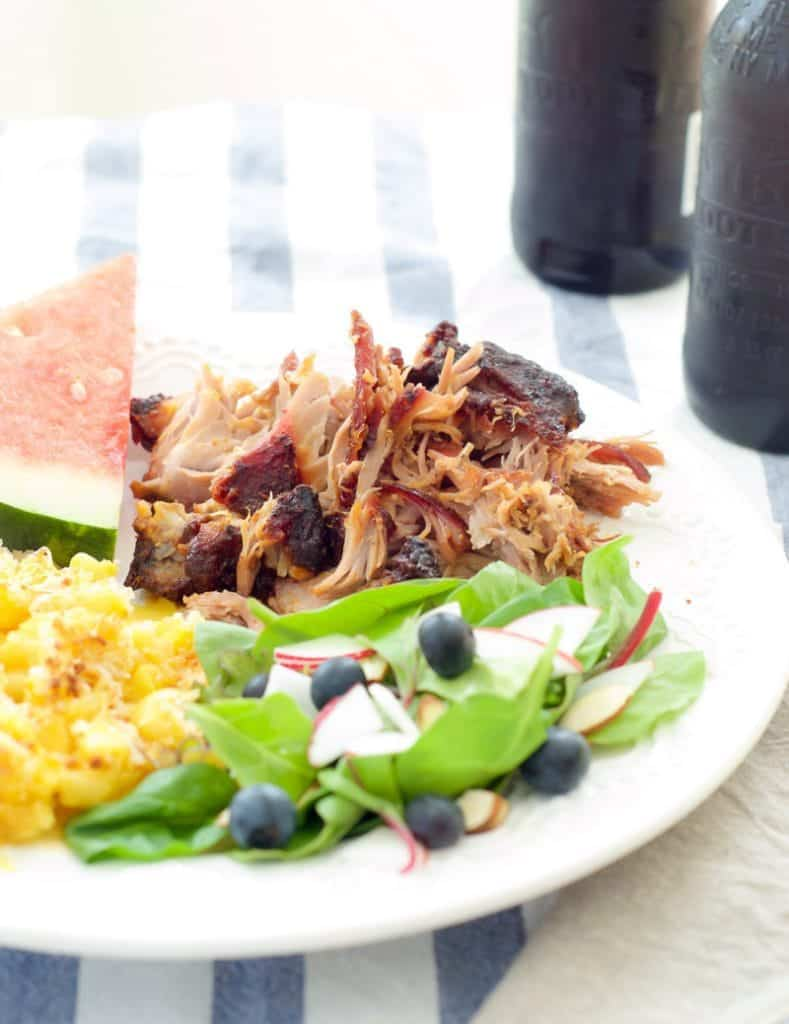 close up shot of pulled pork on plate with salad, macaroni and cheese, and watermelon
