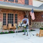 man sawing something on table outside a brick home