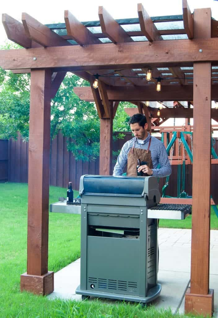 Man in apron grilling outdoors