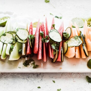tray of melon slices and cucumber slices topped with lime juice and cilantro