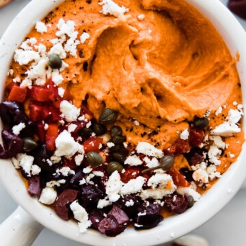 bowl of roasted red pepper hummus with feta olives on top