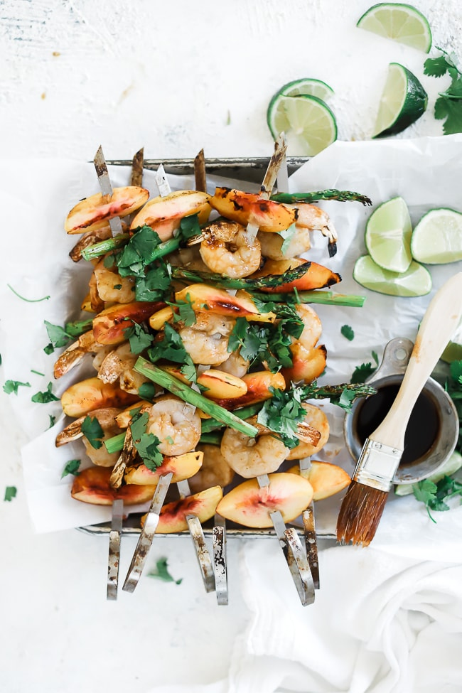 Several shrimp kabobs on a sheet plan with white parchment paper. There are lime wedges and a bowl of marinade to the side.