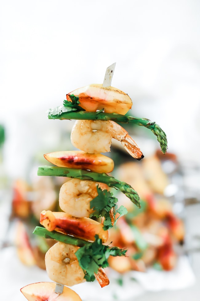 A close up of peach and grilled shrimp kabobs.