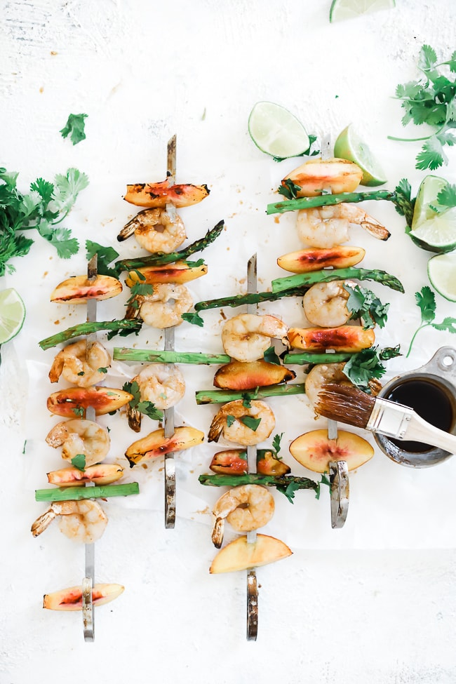 Peach skewers on a white counter. They are slayed out with cilantro and limes.