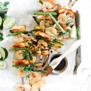 Peach and grilled shrimp kabobs on a sheet pan lined with white parchment paper. There is a small bowl of marinade to the side.