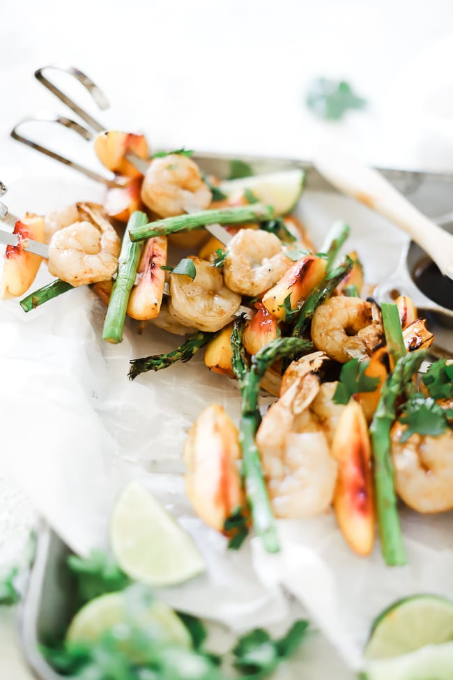 Shrimp skewers on a sheet pan lined with white parchment paper. There are lime wedges and cilantro for garnish.