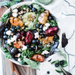 Stone fruit grilled salad in a white bowl, atop a wooden cutting board.