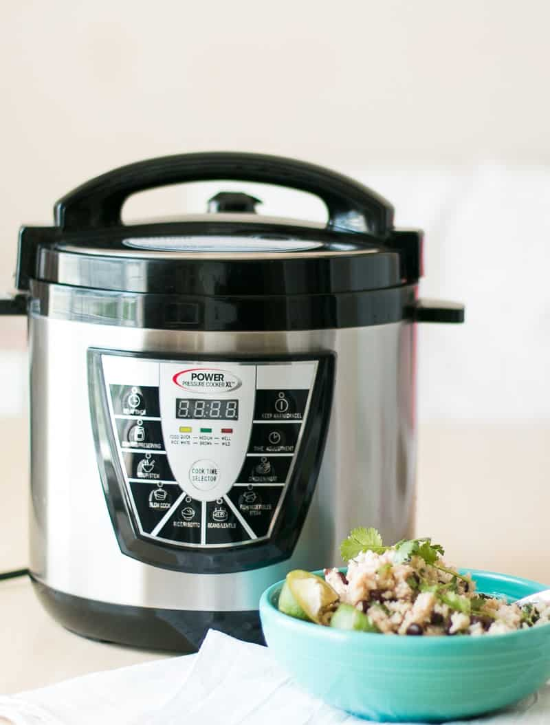 A Pressure Cooker with a blue bowl of Black Beans and Rice next to it