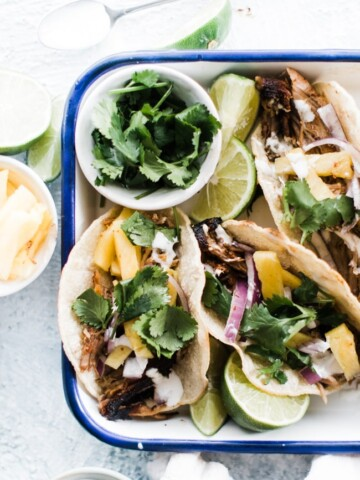 tray of tacos al pastor with limes and cilantro