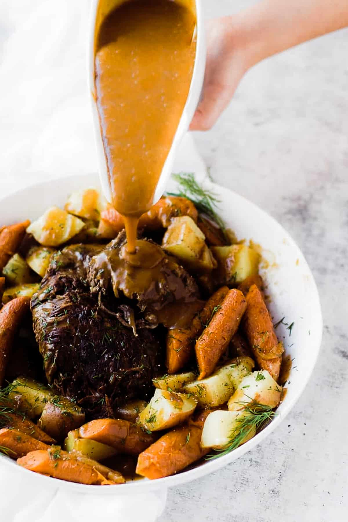 A close up of instant pot roast beef in a large serving platter with vegetables and gravy getting poured over