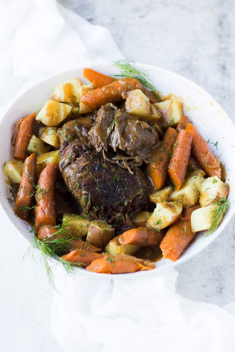 A close up of instant pot roast beef and vegetables in a large white serving bowl sitting on a white surface