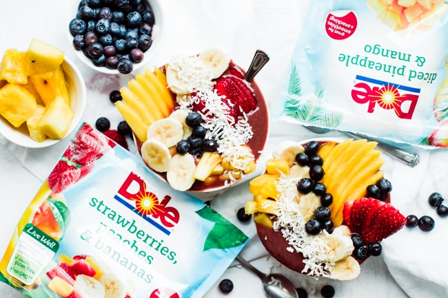 one bowl of acai with fresh fruit, berries and coconut and bags of dole pictured