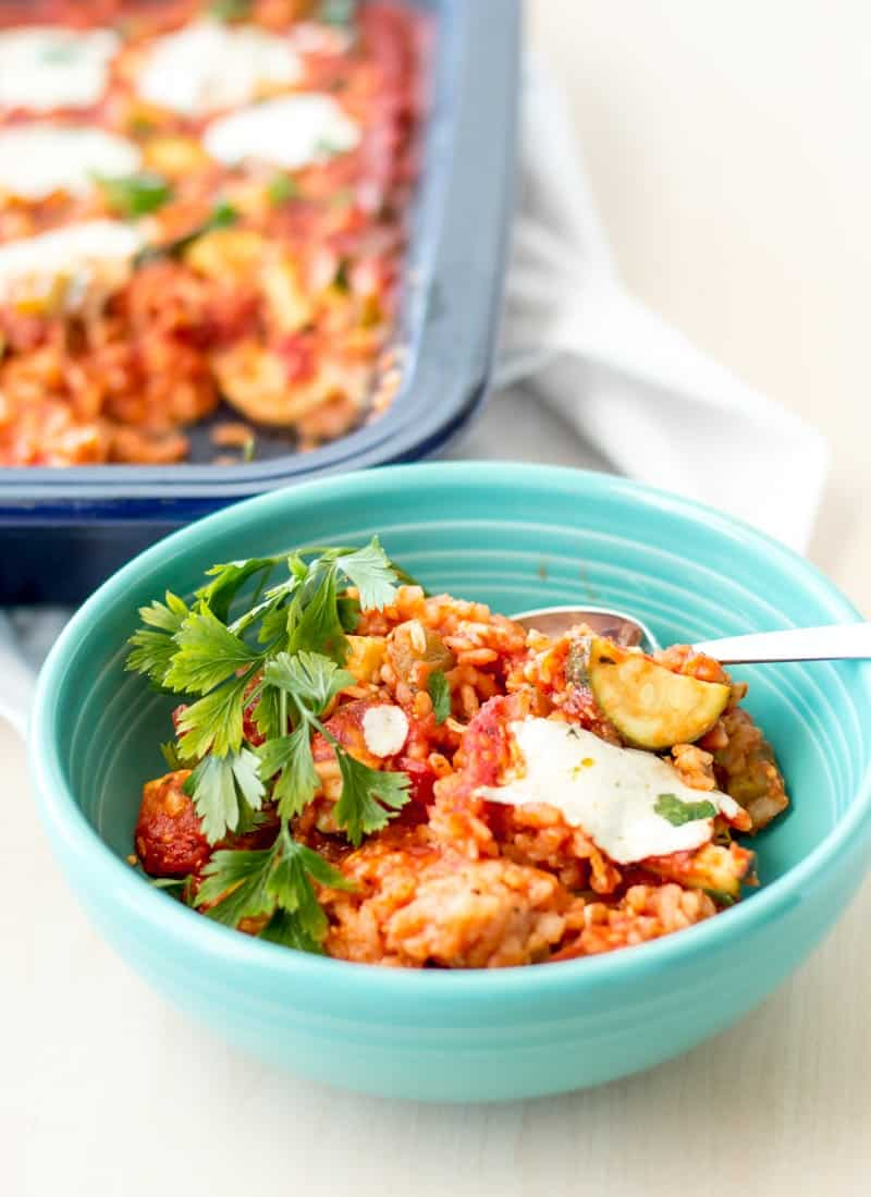 baked-tomato risotto in bowl with green garnish