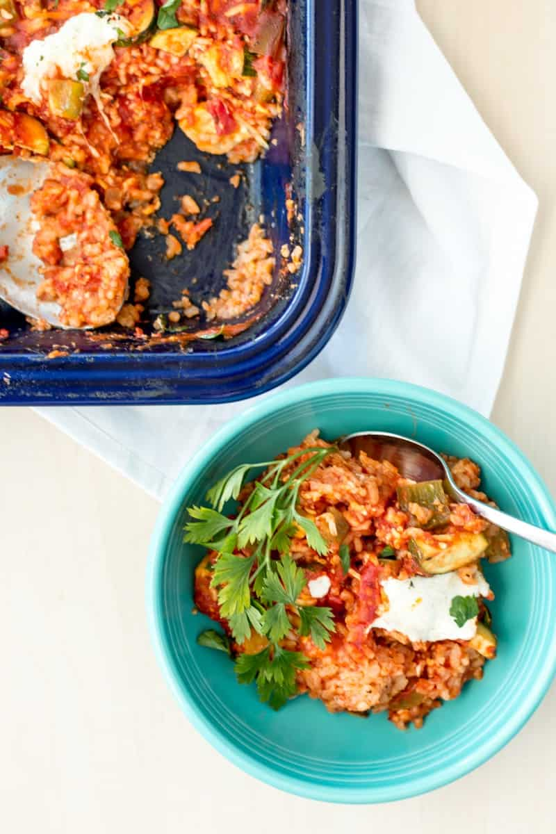 bowl of baked tomato risotto next to baking dish
