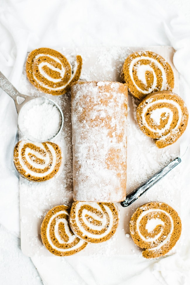 flatlay of pumpkin roll and pumpkin roll slices