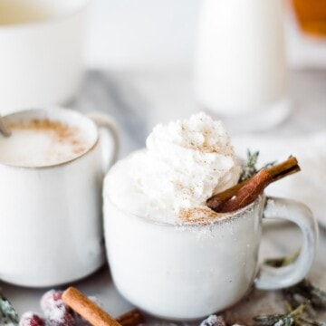 one cup in focus with cinnamon sticks and whipped cream topping