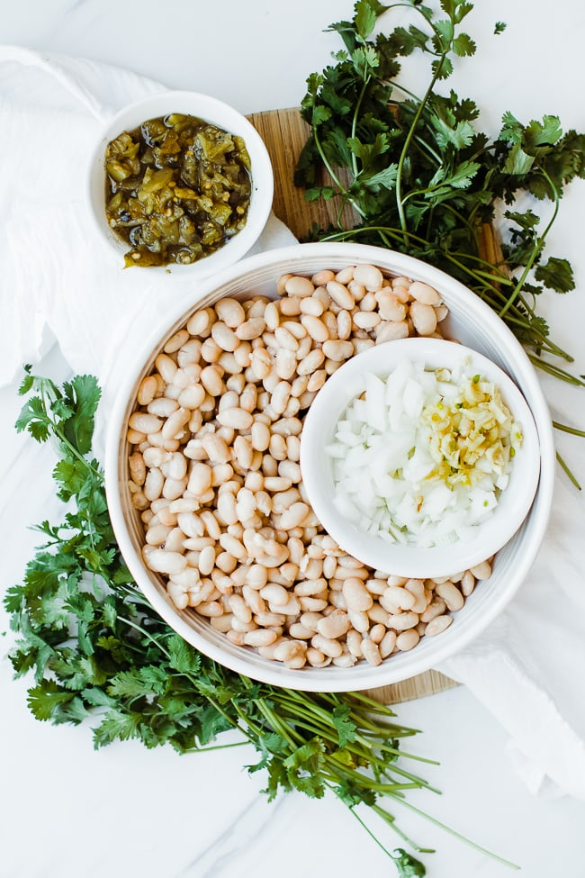 white beans in large bowl, small bowl with onions and garlic, another small bowl with green chili's