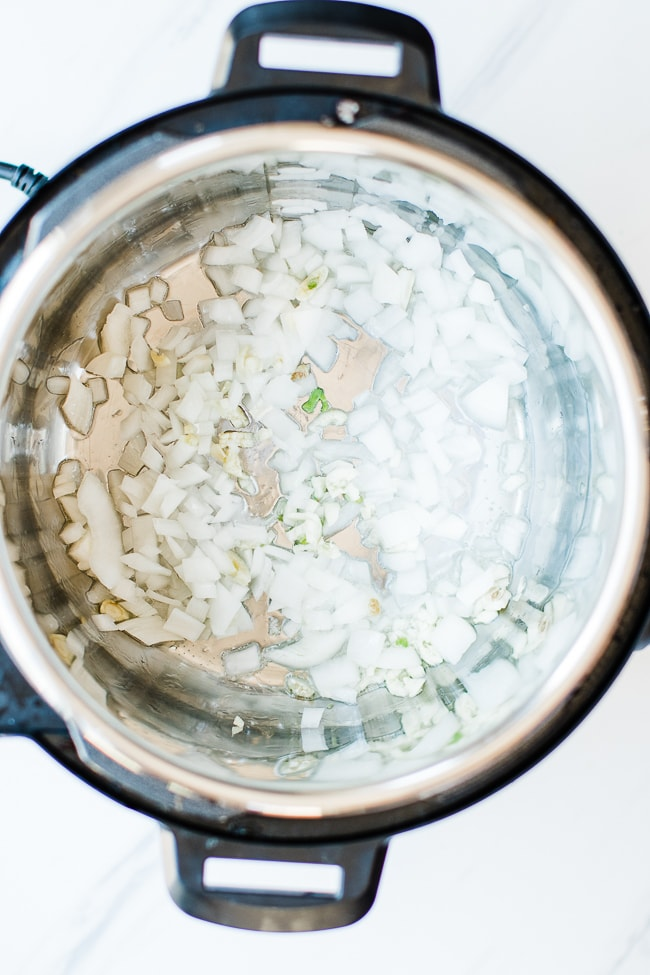 onions and garlic in instant pot sautéing in oil
