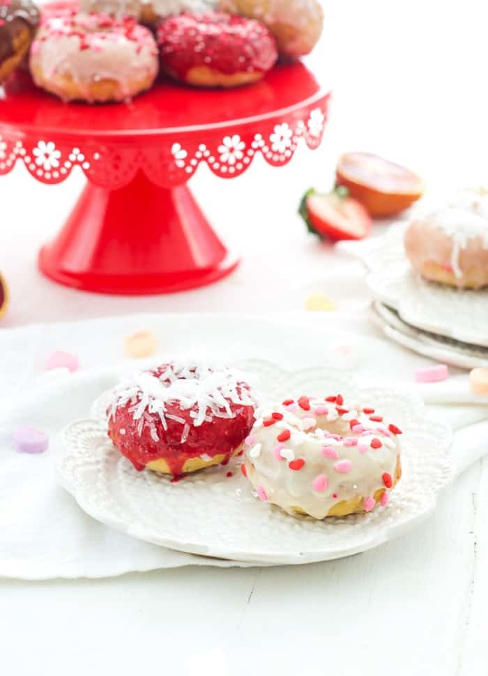Two Valentine's Coconut Cake Doughnuts on a white plate