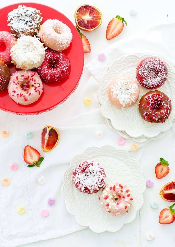 Valentine's Coconut Cake Doughnuts on two white plates and a rd cake stand