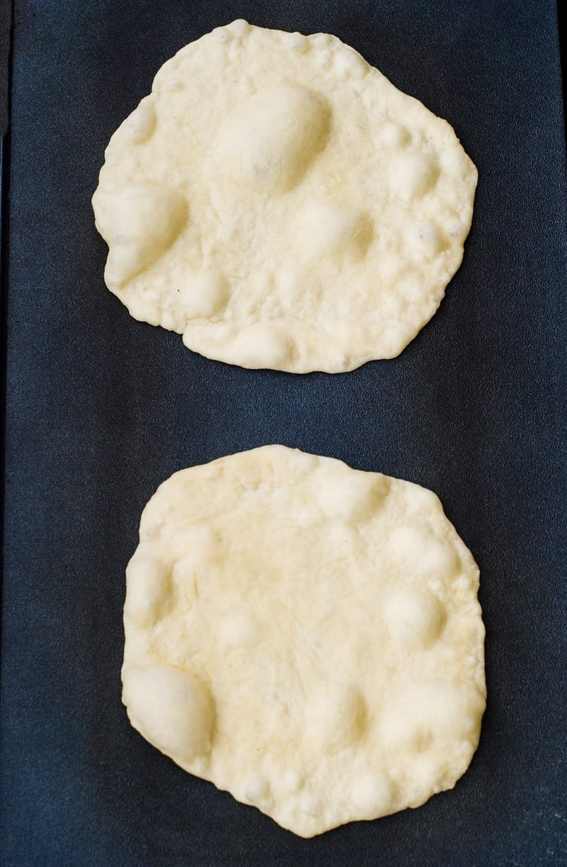 An overhead shot of two homemade flour tortillas on a dark surface