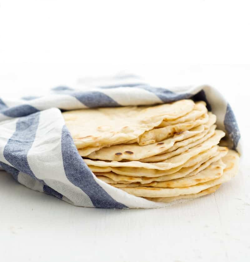 A close up shot of homemade flour tortillas piled on top of each other