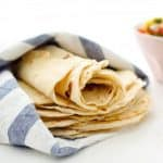 Homemade flour tortillas wrapped in a dish cloth