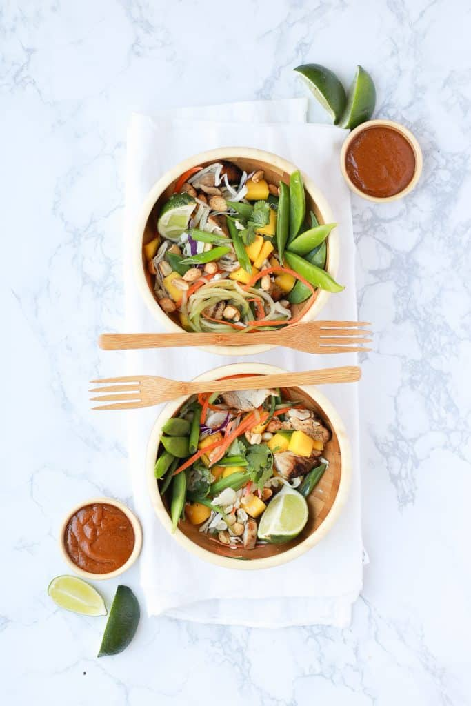 Two thai buddha bowls on a marble surface with wooden forks