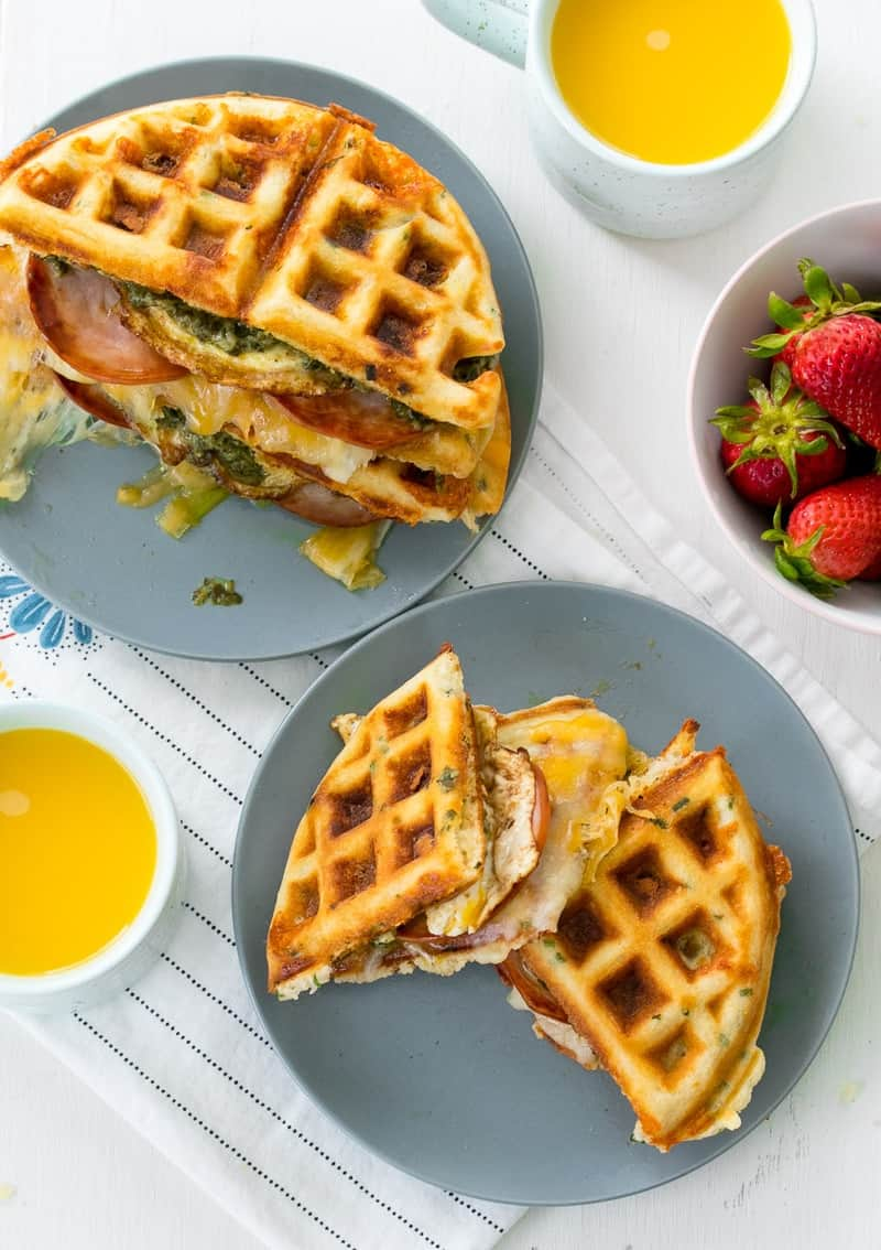 Green Eggs and Ham Waffle Sandwich overhead shot with orange juice in mugs, along with strawberries in a bowl