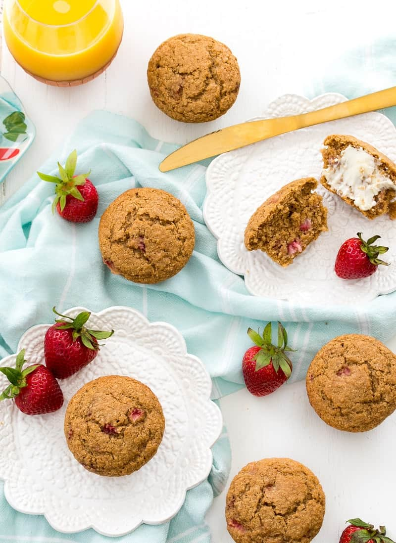 An overhead shot of Strawberry Bran Muffins on a white surface with strawberries
