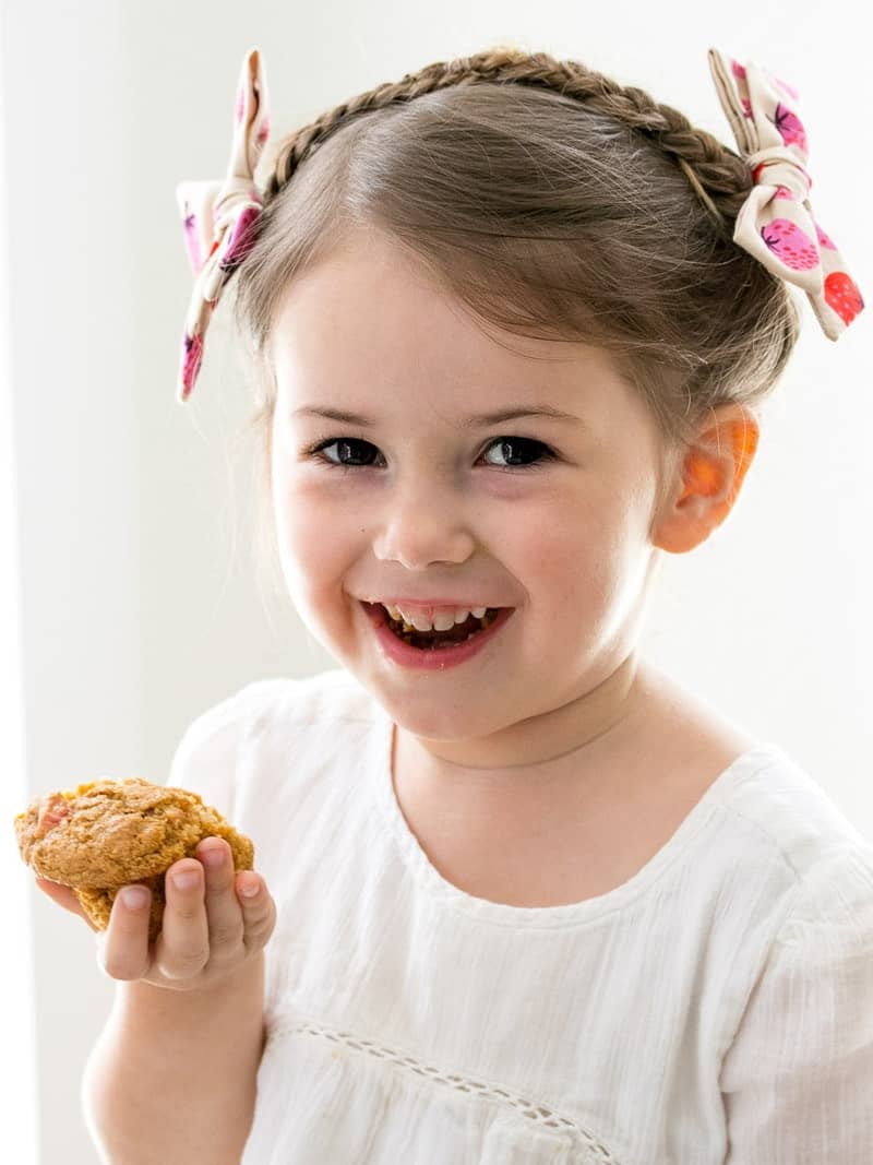 A little girl holding Strawberry Bran Muffins