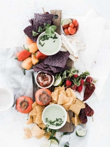 board with bowls of dip and veggies and chip