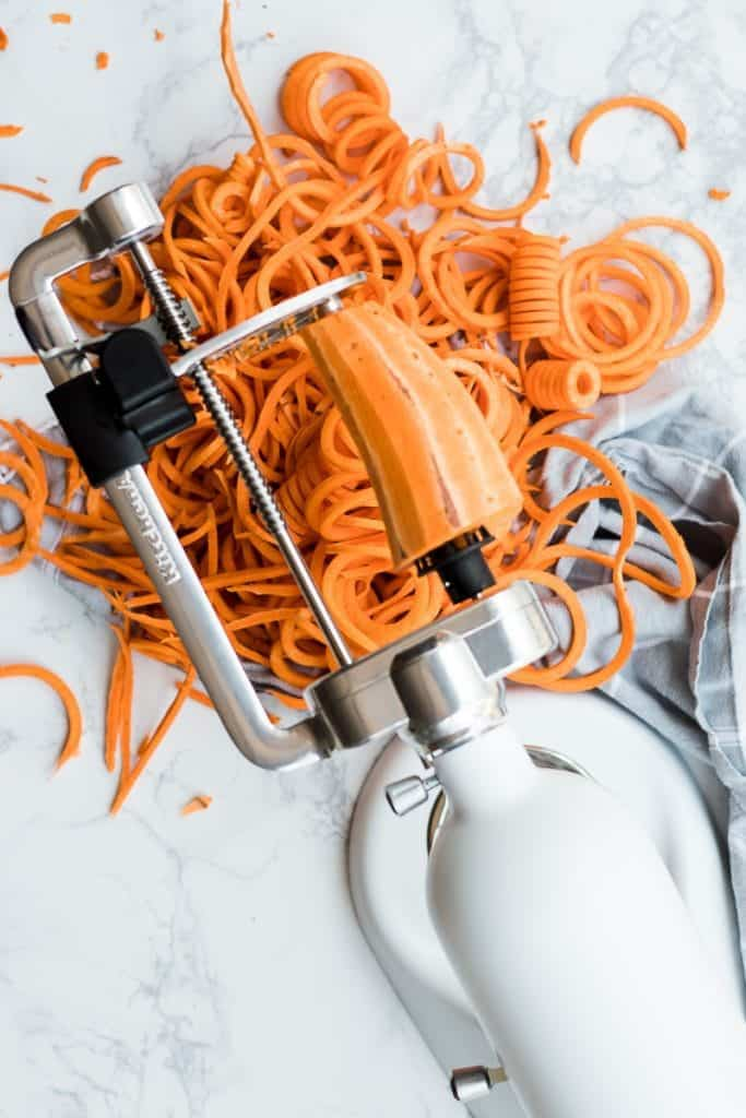 Curly Sweet Potatoes getting cut into spirals with a kitchen aid attachment