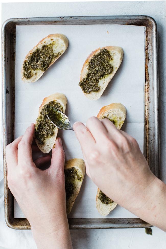 spreading pesto on bread