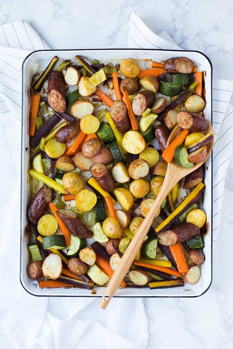 An overhead shot of a Sausage + Veggie Sheet Pan with a wooden spoon
